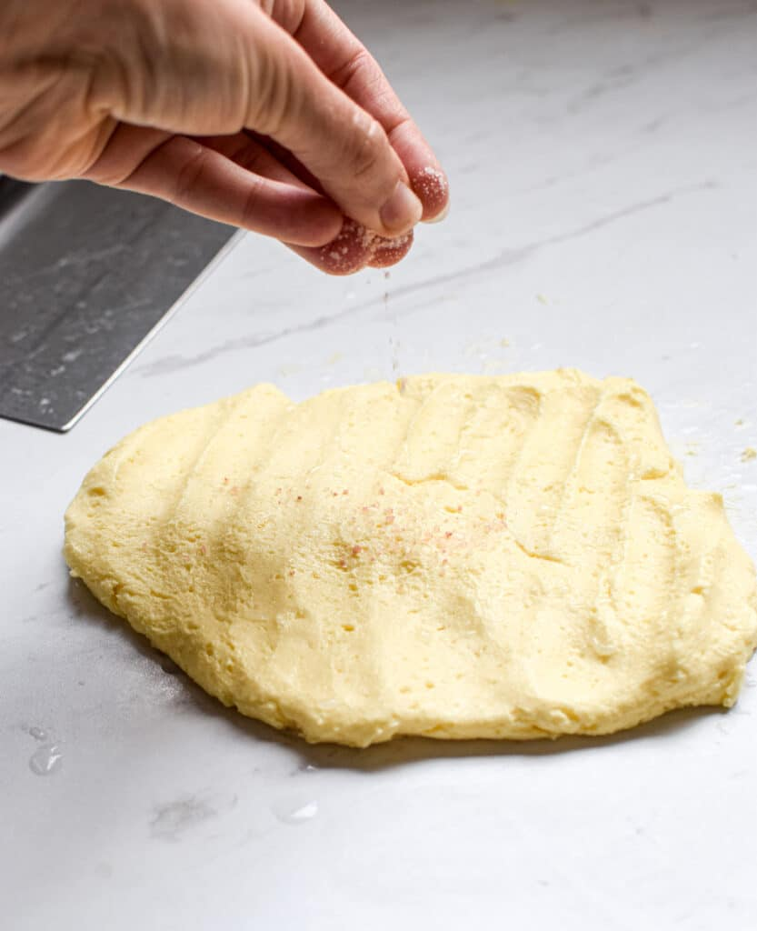 pink salt being sprinkled on top of flattened butter block on a bench with a dough scraper on the left