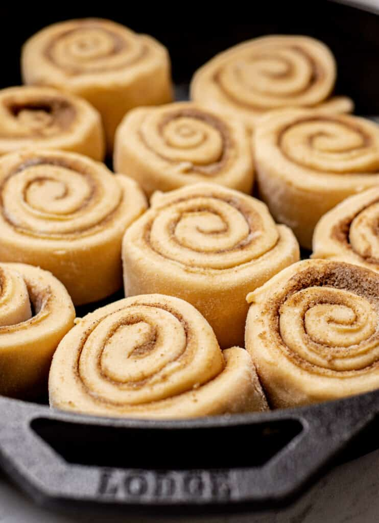 a cast iron pan with dough rolls filled with cinnamon sugar