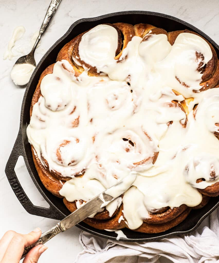 a cast iron pan with baked cinnamon rolls with white icing. A hand is holding a knife and adding on the icing