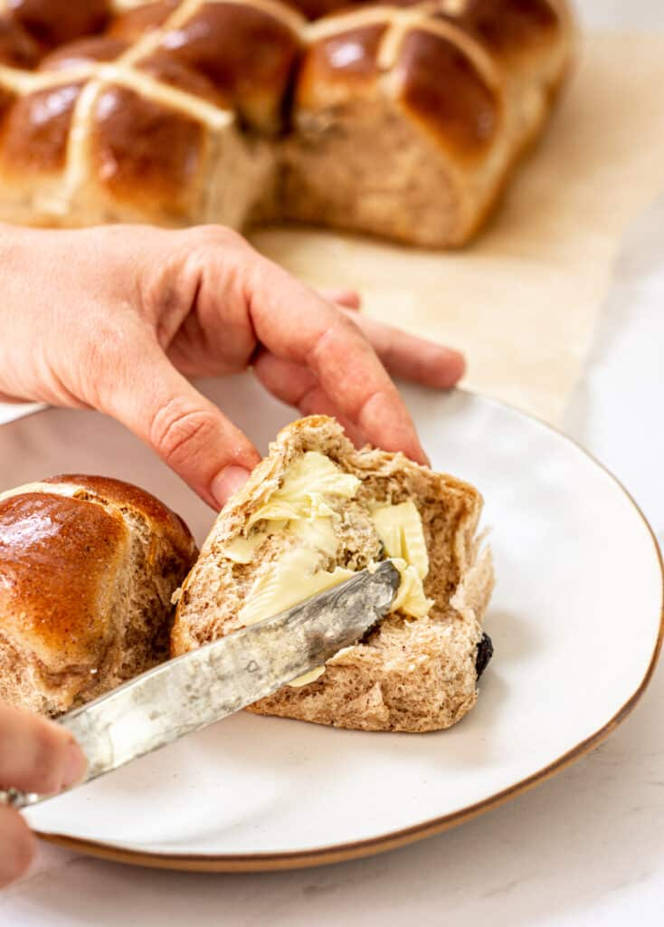 a hand holding a knife, smearing butter over a cut hot cross bun