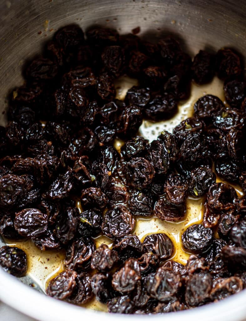 a silver bowl of raisins soaking in orange juice