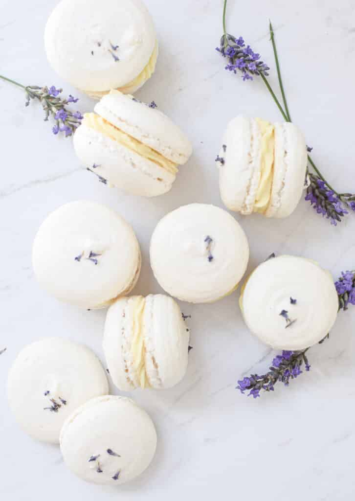 9 6 white macarons with a lemon and white chocolate ganache in the middle.