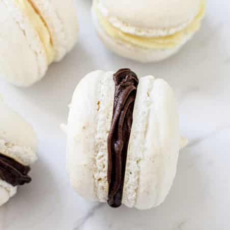 Macarons with dark chocolate ganache and some with white chocolate ganache on a white benchtop