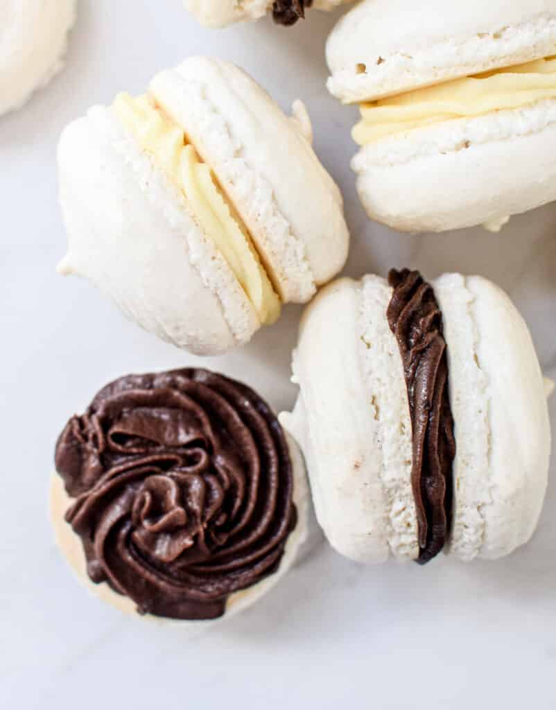 Macarons with dark chocolate ganache and some with white chocolate ganache on a white bench top.