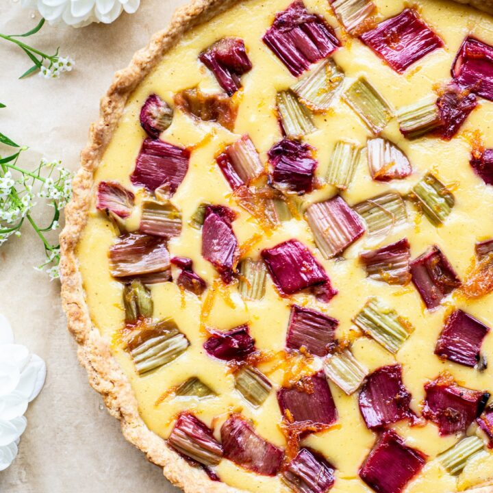 baked rhubarb and custard tart with bright red rhubarb pieces against a yellow custard background