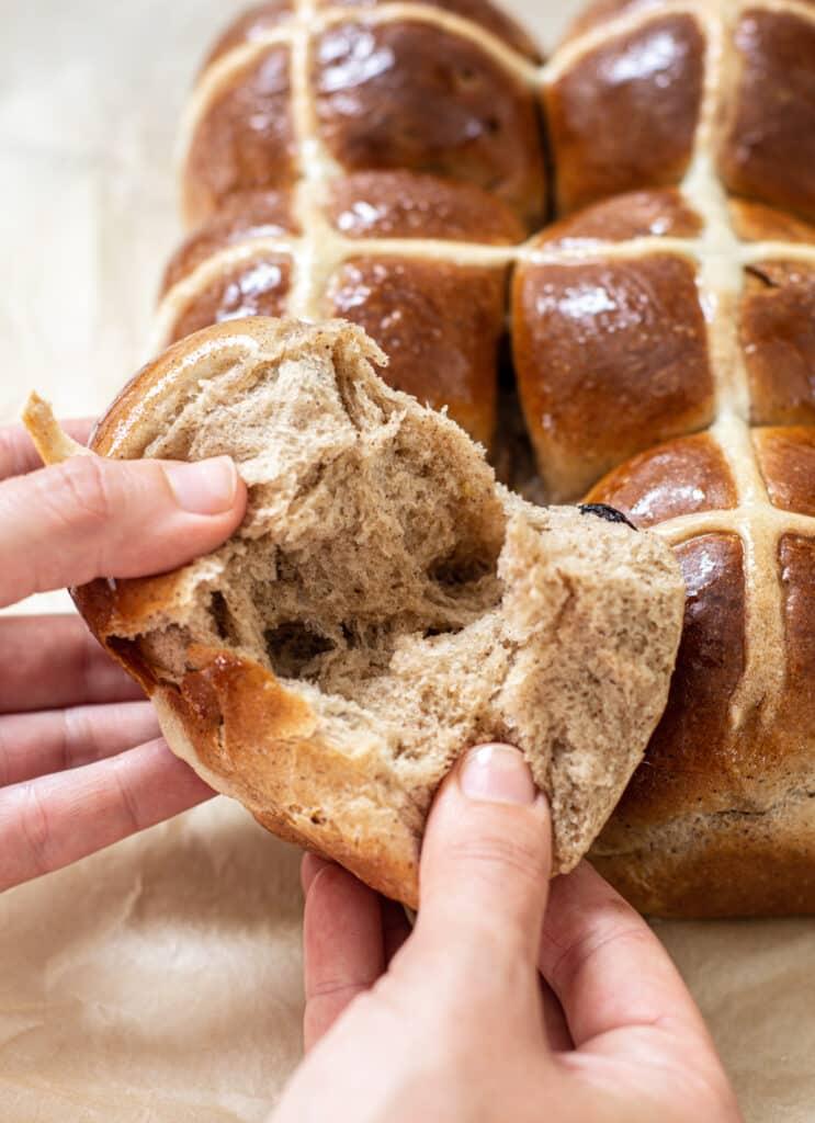 a hand ripping open a hot cross bun