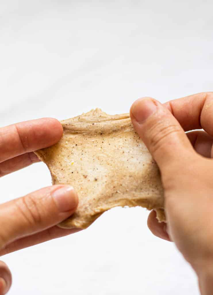 a piece of dough being stretched very thin between two hands