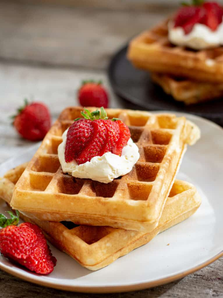 a stack of two waffles on a white plate topped with cream and sliced strawberries