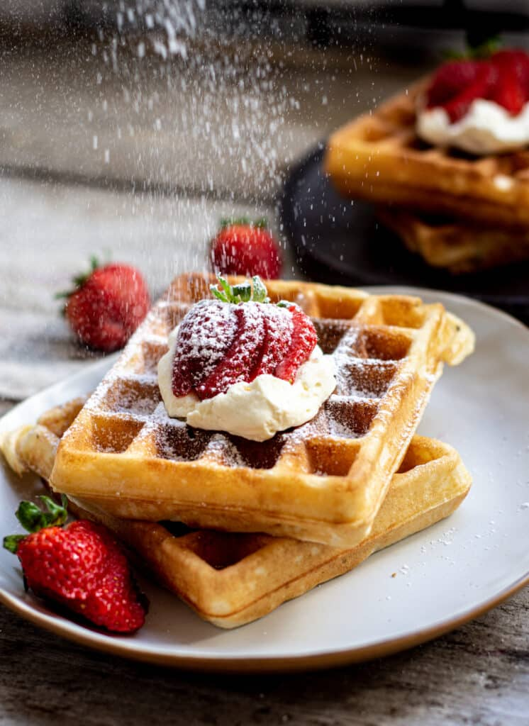 a stack of two waffles on a white plate topped with cream and sliced strawberries. dusted with icing sugar, a black plate with waffles in the background