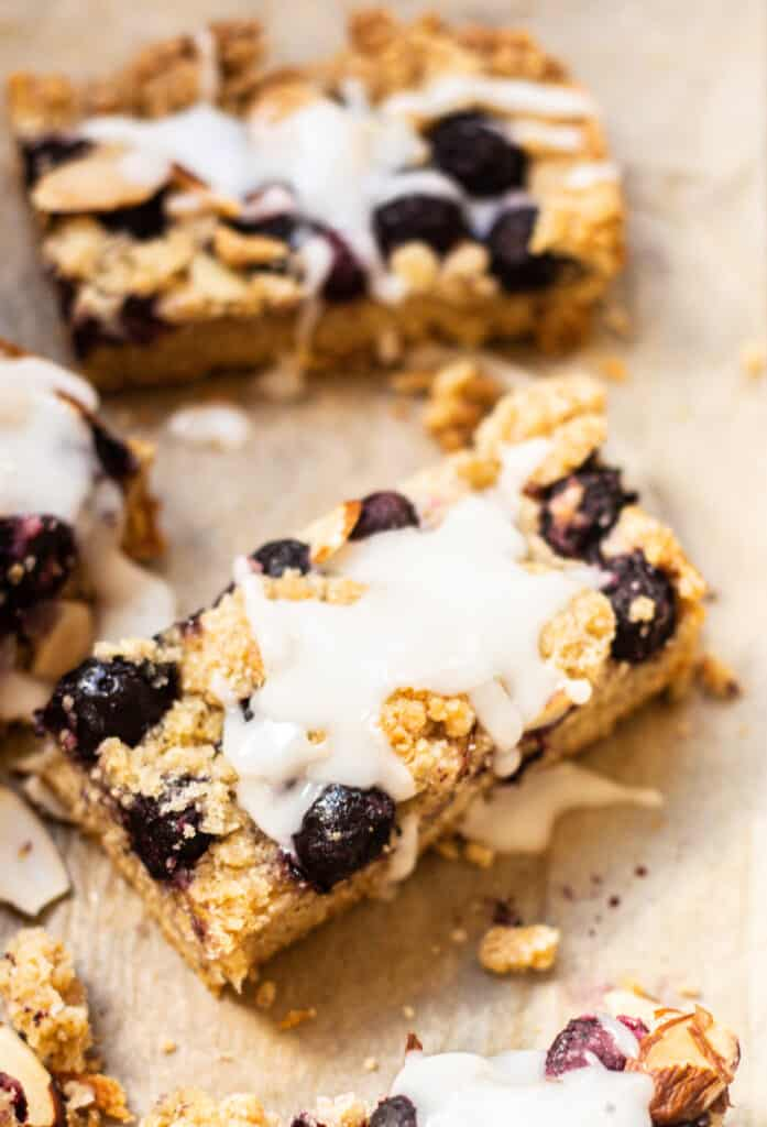 glazed blueberry crumble bars on brown paper