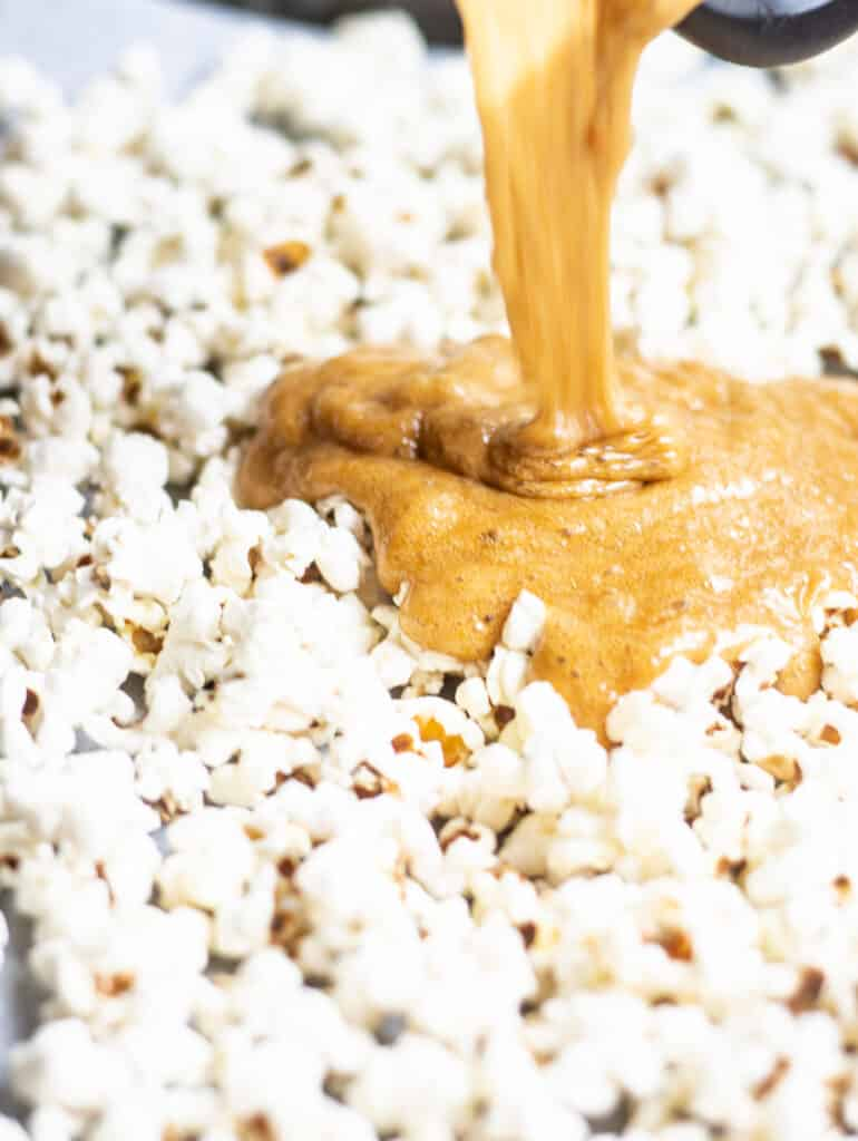 caramel being poured over popcorn