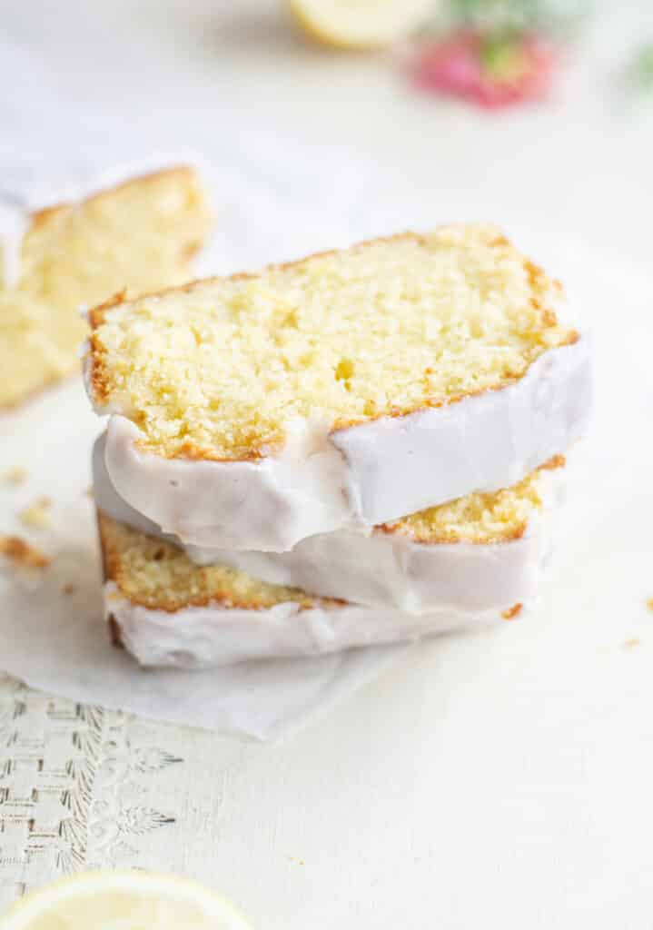 stacked lemon loaf slices with white icing flowers in the background