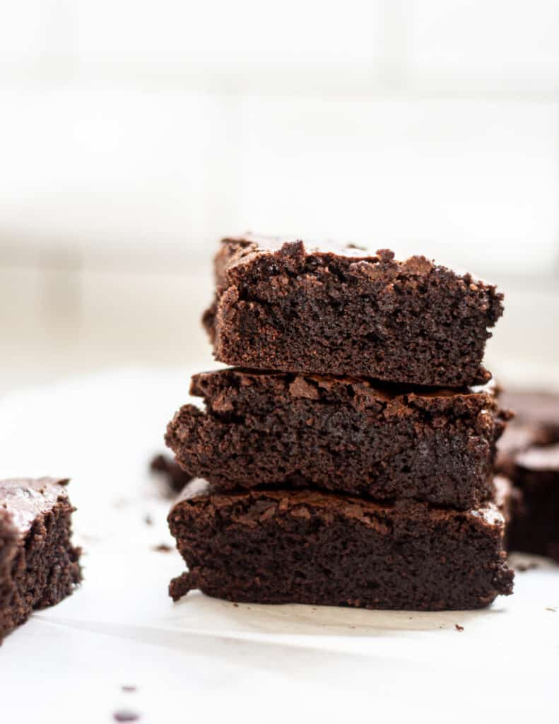 chocolate brownies on white parchment paper, stacked