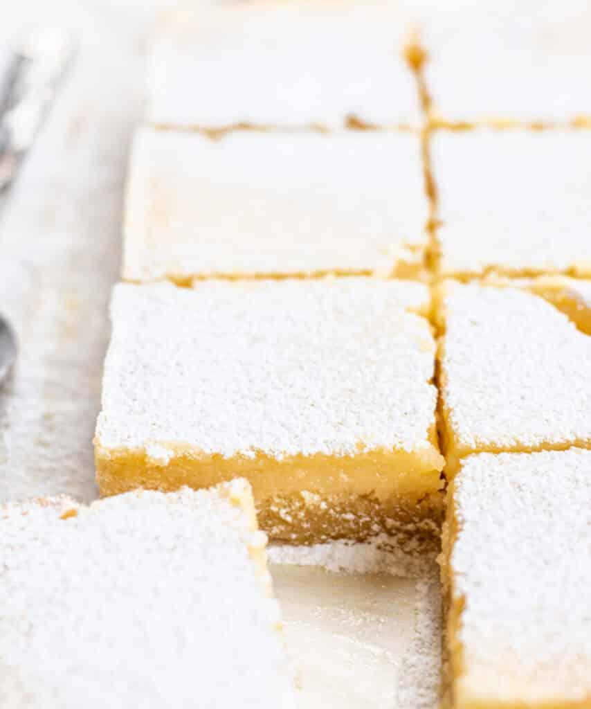 8 lemon bars cut into squares on parchment paper
