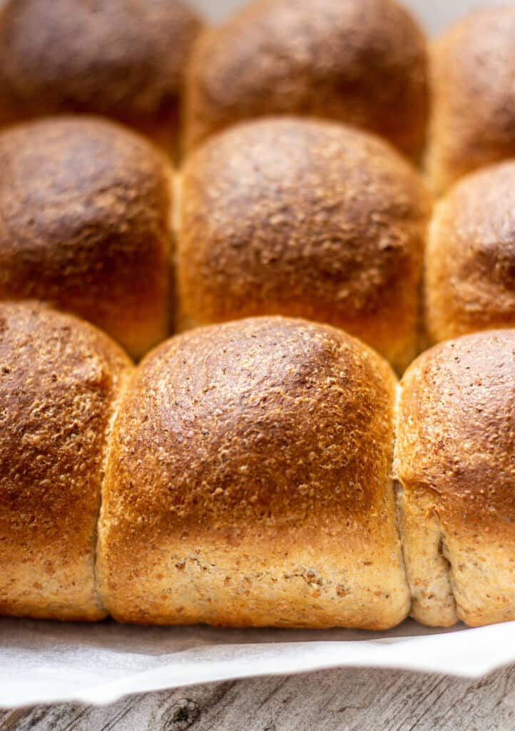 close up of wholewheat pull apart rolls on white paper and wooden board