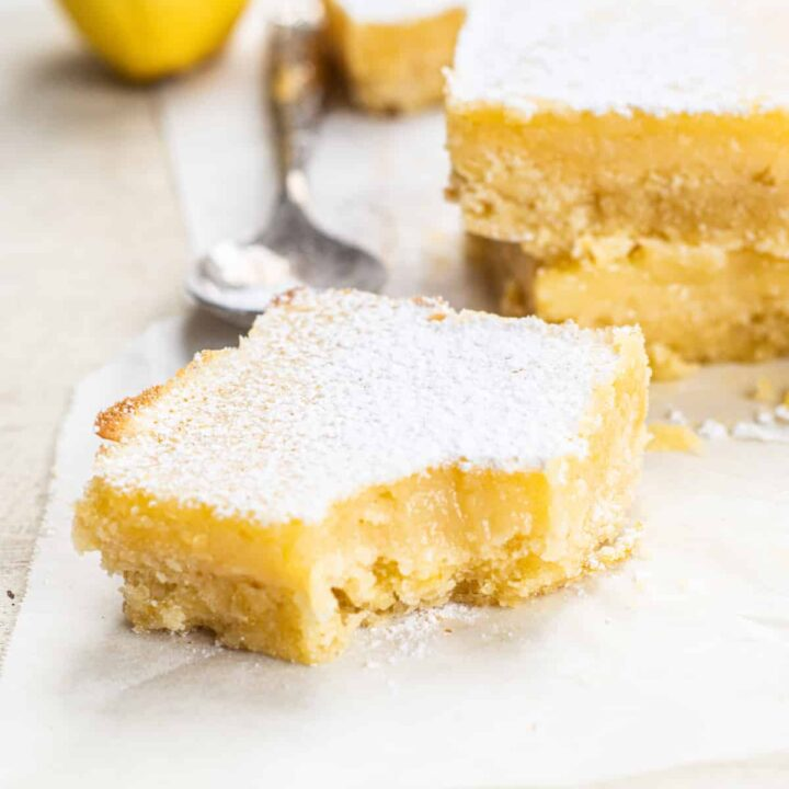 a slice of yellow lemon bar with a bite out of it