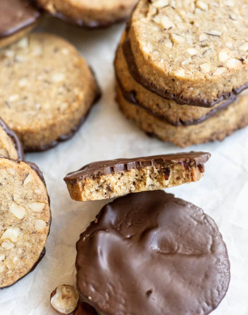 stacks of hazelnut cookies with one bitten in half