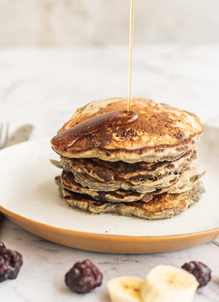 syrup being poured over pancakes
