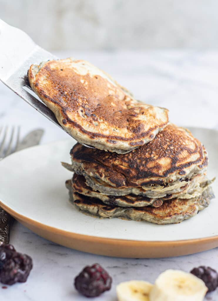 a spatula placing a pancake on a stack